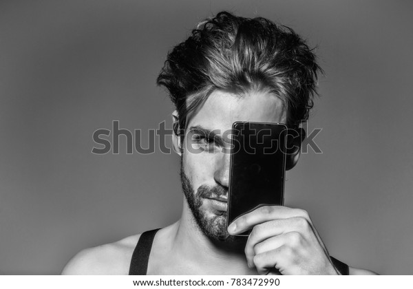 Handsome man confident fashion sexy young blond bearded male model with suspenders on topless sexi nude torso hides face behind smartphone or mobile phone on grey background
