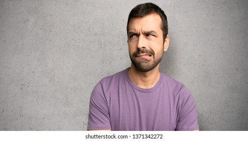 Handsome man with confuse face expression while bites lip over textured wall