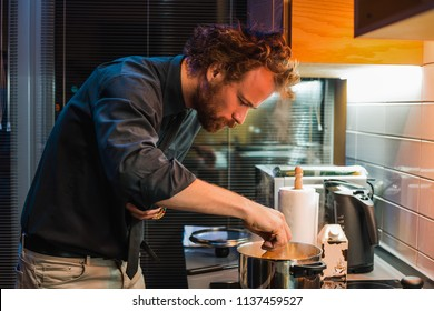 Handsome man cooking at the kitchen, man curly hair style, man in black shirt, bearded man, home party, prepare dinner, pan, pasta, kettle, delicious, food, evening, pretty, seriously, concentration