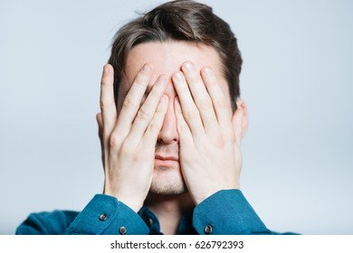 Handsome man covers face with hands, isolated on a gray background
