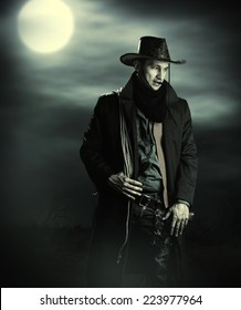 Handsome man in cowboy costume stay in steppe at night with full moon. Vampire Hunter