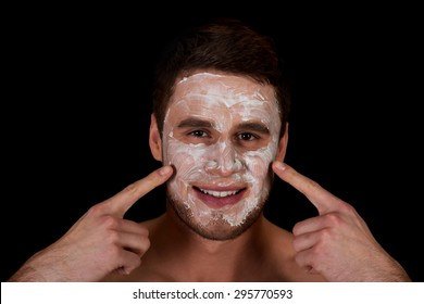 Handsome man with cream moisturizer on his face.