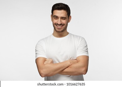 Handsome man with crossed arms smiling and winking, looking at camera isolated on gray background