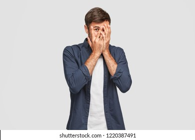 Handsome man with dark hair, bristle, hides face with hands, peeks through fingers, wears fashionable shirt, feels shy, isolated over white background. Curious guy cannot to look at present.