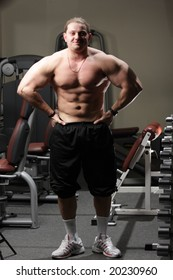 Handsome man demonstrating thews in gymnasium