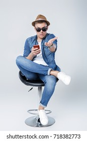 handsome man in denim sits on chair with phone on white background