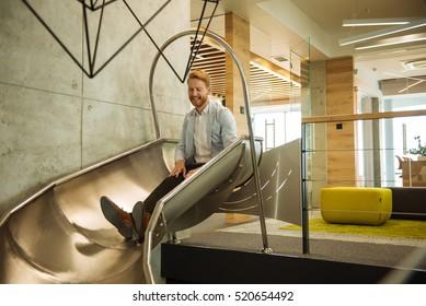 Handsome man descending on a toboggan in the office.
