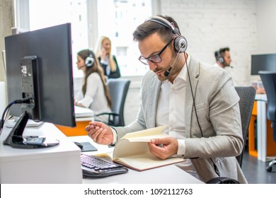 Handsome man dispatcher taking notes while talking with customer in office.