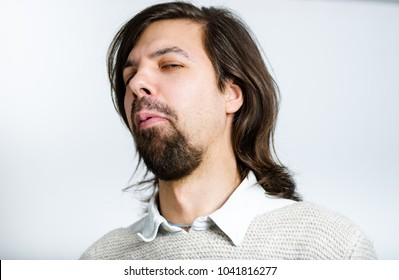 A handsome man does an unhappy look, with long hair, isolated studio photo