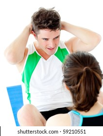 Handsome man doing fitness exercises with a woman in gym