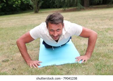 Handsome man doing fitness exercises outside