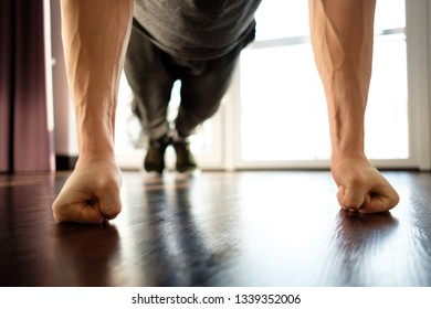 A handsome man doing plank exercises against the window of a house