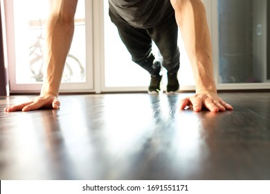 A handsome man doing plank exercises push ups against the window of a house