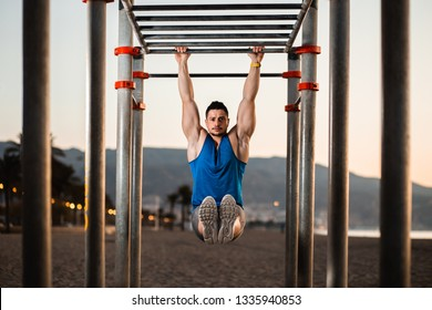 Handsome man doing pull-ups at outside training park