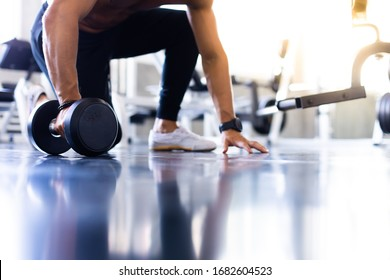 handsome man doing push ups exercise with one hand in fitness gym