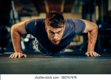 Handsome man doing pushups in the gym