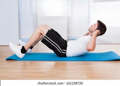 Handsome Man Doing Sit-ups On A Blue Exercise Mat
