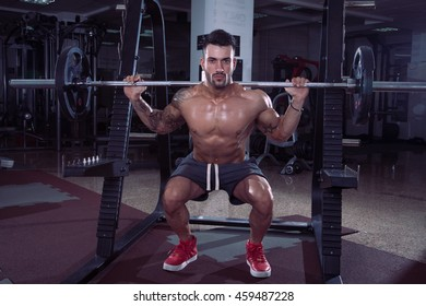 Handsome man doing squats in gym.