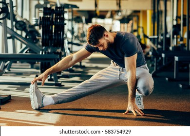 Handsome man doing warm up in the gym and stretch legs