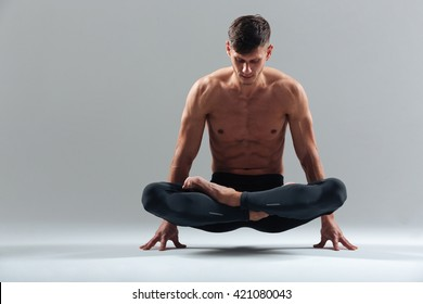 Handsome Man Doing Yoga Exercises Isolated On A White Background