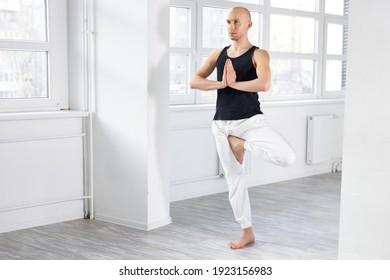 handsome man doing yoga position, tree pose. young caucasian guy keep calm, hold hands together, standing on one leg. in bright studio room alone, in sporitve clothes