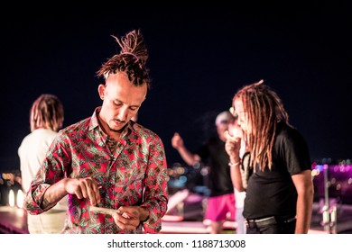 Handsome man with dreadlocks on party rolling weed joint of marijuana. Legalise it.