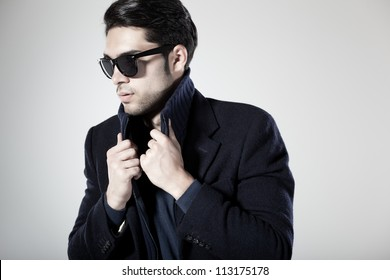 handsome man dressed casual with sun-glasses posing in the studio