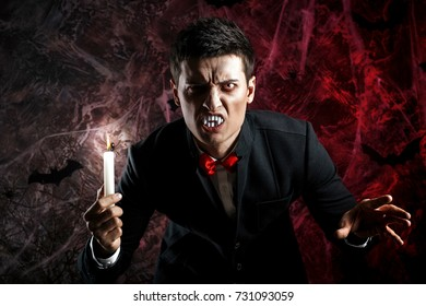 handsome man dressed in a Dracula costume for Halloween.   horrific vampire with candles
