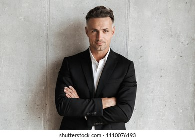Handsome man dressed in suit holding arms folded and looking at camera over gray wall background