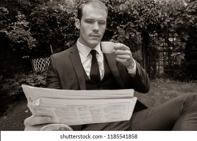 Handsome man dressed in vintage classical suit drinking coffee at cafe table while reading newspaper