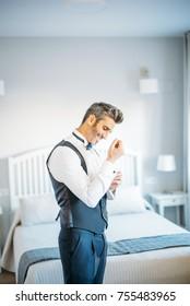 Handsome man dresses in hotel room.
