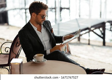 Handsome man drinking coffee and reading newspaper in coffee shop