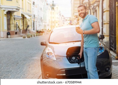 Handsome man drinking coffee while charging electric car