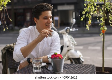 Handsome man drinking espresso in coffee bar outdoors.