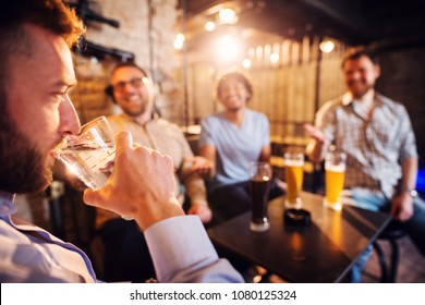Handsome man drinking a glass of water in the local pub while his friends laughing with a beer in front.