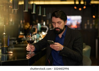 Handsome man drinking glass of wine in a bar and checking smartphone