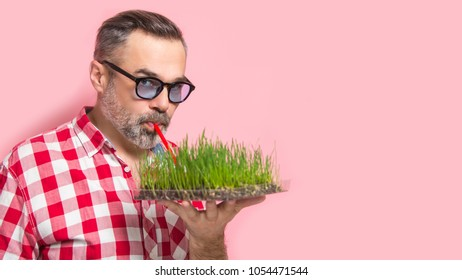 Handsome man drinking homegrown wheatgrass drink concept over pink background