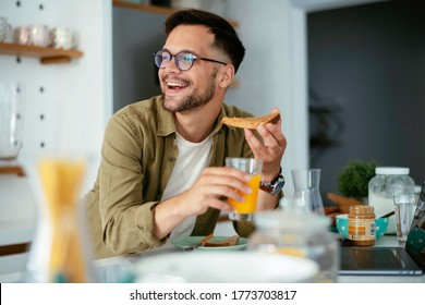 Handsome man drinking juice in kitchen. Young man eating breakfast at hoe.