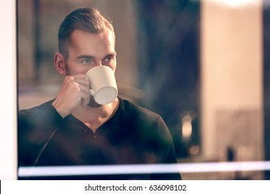 Handsome man drinking from a mug looking out of the window from inside house, wearing a black shirt.