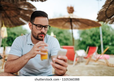 Handsome man drinking orange juice and using smartphone on the beach.
