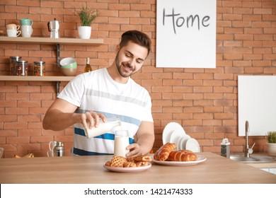 Handsome man drinking tasty milk in kitchen at home