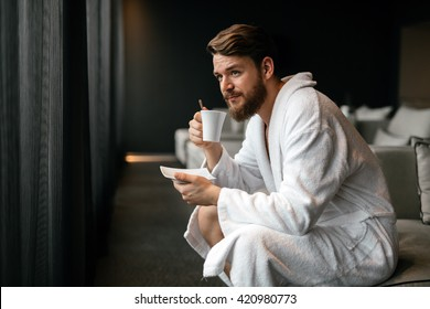Handsome man drinking tea and relaxing in bathrobe
