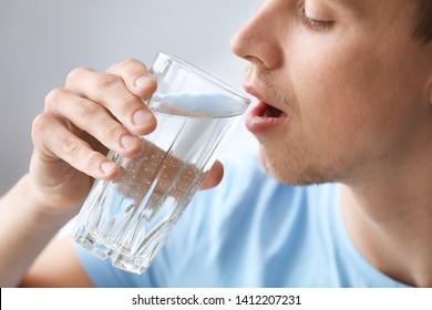 Handsome man drinking water at home, closeup