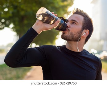handsome man drinking water on a sunny day