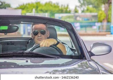 A handsome man driving  cabriolet  car and wearing sunglasses