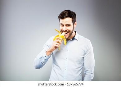 handsome man eating a banana