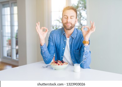 Handsome man eating cereals for breakfast at home relax and smiling with eyes closed doing meditation gesture with fingers. Yoga concept.