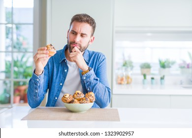 Handsome man eating chocolate chips muffin serious face thinking about question, very confused idea