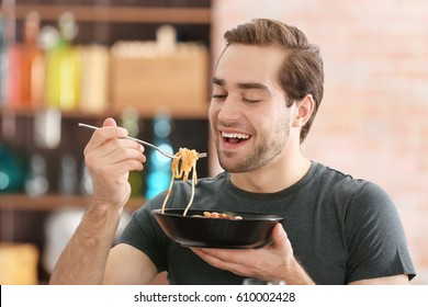 Handsome man eating pasta at home