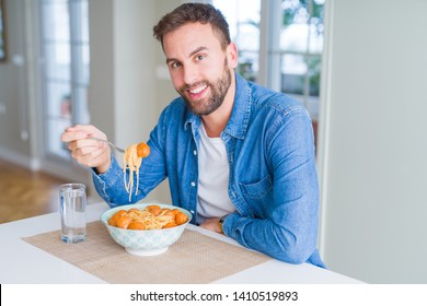 Handsome man eating pasta with meatballs and tomato sauce at home while smiling at the camera